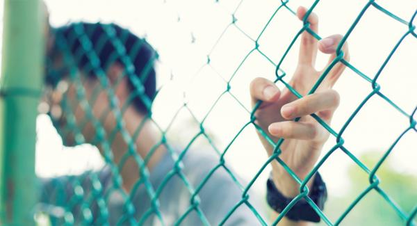 man clinging to wire fence